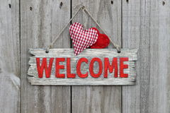 Red welcome sign hanging on wood door with gingham heart Royalty Free Stock Image