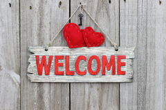 Red welcome sign hanging on wood door with red hearts and iron keys Royalty Free Stock Photos