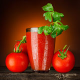 Red and wet!. A wet glass of tomato juice decorated with parsley and ripe tomato bunch on a wooden table Royalty Free Stock Photography