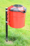 Red and wet garbage basket in a park on a background of green grass Royalty Free Stock Photography
