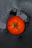 Red wet tomato. Tomato on a black background with water drops Stock Photo