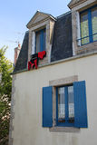 A red wetsuit is drying at the window of a house (France) Royalty Free Stock Image