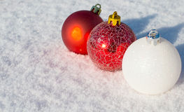 Red and whait christmas balls. Colored Christmas balls on white snow Royalty Free Stock Image