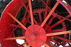 Red wheel. An antique tractor wheel from a steam operated tractor.  whee3l is painted a bright red with yellow trim on the heavy steel spokes Royalty Free Stock Image