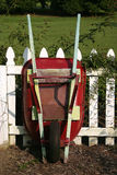 Red Wheel Barrow. A red wheel barrow leaning against a white picket fence Royalty Free Stock Photos