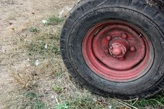 Red wheel of an old tractor on the village ground. Autumn harvest time. royalty free stock image