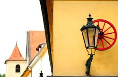Red wheel and streetlight on a medieval building. Decorative element in the form of red wheel and streetlight on a medieval building in the center of Prague Stock Photos