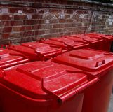 Red wheelie bin lids. A row of red wheelie bins against a red brick wall Stock Images