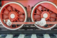 Red wheels closeup vintage locomotive. Big red wheels a closeup of the vintage locomotive with the steam engine on railway tracks Royalty Free Stock Photo