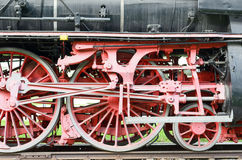 Red wheels and pistons on an old locomotive Stock Photos