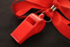 Red Whistle. Attached to red neck ribbon on a  black background Stock Photos