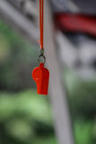 Red whistle in blurry background. This item is for kids used as toy or could be used to indicate and warn if some dangers are coming Royalty Free Stock Images