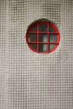 Red on white. Red circle window on a rough texture wall Royalty Free Stock Image