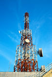 Red and white antenna (cellular tower) under blue sky. Royalty Free Stock Photos