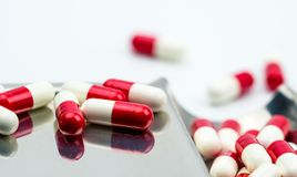 Red, white antibiotic capsules pills with shadow on stainless steel drug tray, drug resistance concept. Stock Photo
