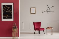 Red and white apartment interior. Gold table against red wall with black poster in apartment interior with armchair against white wall stock photos