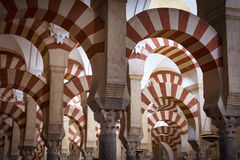 Red and white arches in mosque-cathedral of Cordoba in Andalusia. The famous alternating red and white stonework inside the Moorish mosque-cathedral Stock Images