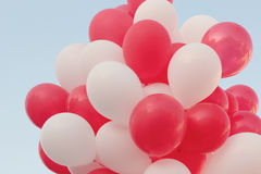 Red and white balloons. A group of red and white balloons against the sky Royalty Free Stock Photography