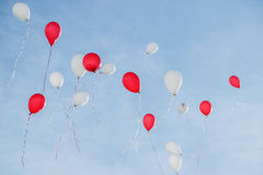 Red and white balloons are released and rise into the blue sky Royalty Free Stock Images