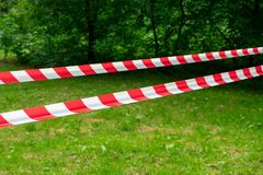 Red and white barrier line on the road in the park stock photos