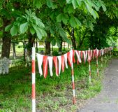 Red and white barrier tape blocking the way stock photography