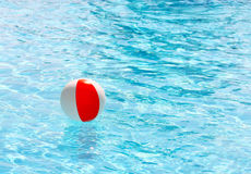 Red White Beach Ball. Beach ball floating in a swimming pool on a hot summer day royalty free stock photos