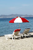 Red-white beach umbrella and chaise lounges on the beach of the Royalty Free Stock Photo