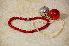 Red and white beads are laid out in form of two hearts next to Christmas toys on beige blanket royalty free stock image