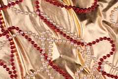 Red and white beads lying on a golden fabric Stock Image
