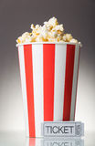 Red and white big cup of popcorn with movie tickets on a gray. Background Stock Photography