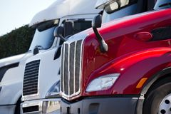 Red and white big rig semi trucks with grilles standing in line. Bright red and White Big rigs semi trucks of different makes and models stand in row on truck Royalty Free Stock Image