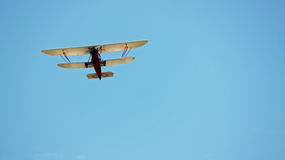 Red and White Biplane Flying in a Blue Sky Stock Photo