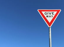 Red, white and black give way sign in a cloudless blue sky Royalty Free Stock Photos