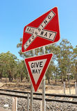 Red, white and black Railway Crossing and Give Way signs Stock Images