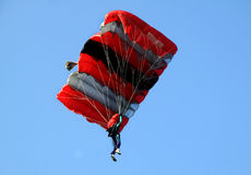 Red white and black sail parachute. On blue sky Stock Photos