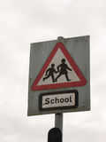 a red white and black school crossing sign with a cloudy sky background royalty free stock photo