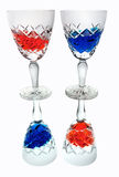 Red white blue. Two crystal glasses, filled with red and blue liquid, reflected in reverse Stock Photos