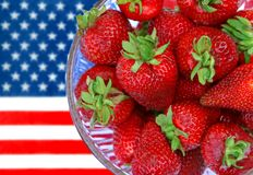 Red White and Blue. Bowl of fresh strawberries with American flag in background Stock Images