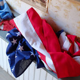 Red white and blue. An American Flag of Red white and blue laying furled on a window sill Stock Photos