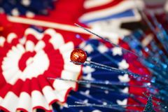 Red White and Blue background with stars and stripes in a blurred bokeh background with glitter objects in foreground. A Red White and Blue background with stars Royalty Free Stock Photos