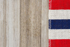 Red, white and blue burlap ribbon on weathered wood background stock photos