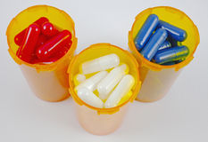 Red, white, and blue capsules in pill bottles Stock Photography