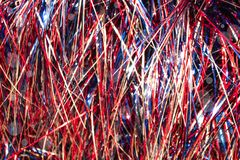 Red white and blue cellophane tinsel strips background with bokeh. A Red white and blue cellophane tinsel strips background with bokeh Royalty Free Stock Image