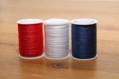Red white and blue cotton reels or bobbins on a wooden needlewor Stock Photo