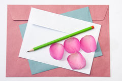 Red white and blue envelope with a wooden pen and pink rose peta Stock Image