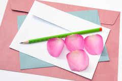 Red white and blue envelope with a wooden pen and pink rose peta Royalty Free Stock Image