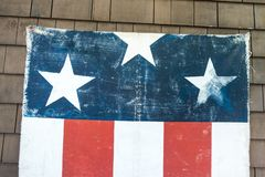Textured distressed hanging american red white and blue flag with three stars and 5 stripes on the side of house wall July 4th. Red white blue flag with three royalty free stock photos