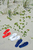 Red white and blue flip flops on the beach. Beach travel concept. Red white and blue flip flops on the sand, perfect for cover art Royalty Free Stock Images