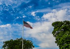The Red, White and Blue and Green!. An American flag as it blows in the breeze with a fluffy cloudy sky and green leaved trees in the background royalty free stock photography