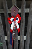 Red, White and Blue Holiday Birdhouse Decoration. Fourth of July ribbons and stars on birdhouse ornament nailed to wooden fence Stock Photos